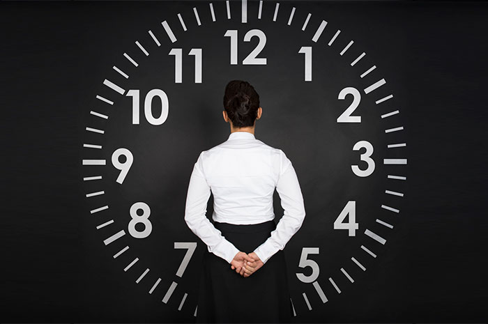 woman in front of clock